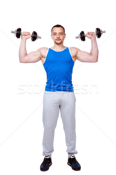 Full-length portrait of a sports man doing exercises with dumbbells over white background Stock photo © deandrobot