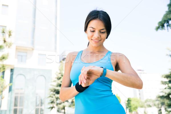 Glücklich sportlich Frau smart ansehen Freien Stock foto © deandrobot