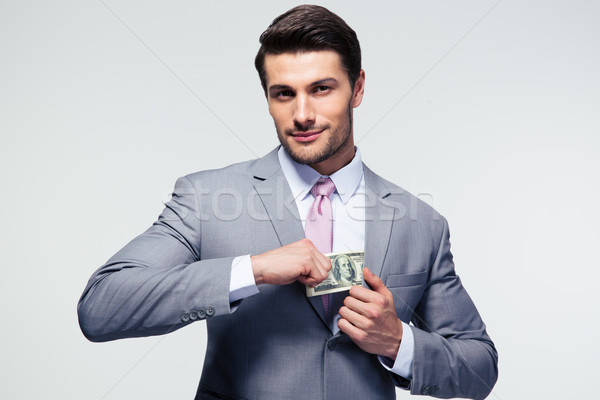 Businessman putting money in pocket Stock photo © deandrobot