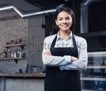 Happy charming female waiter in apron Stock photo © deandrobot