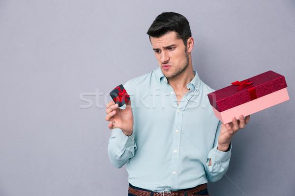 Young man choosing between small and big gift box Stock photo © deandrobot