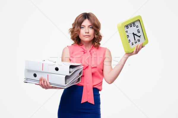 Businesswoman holding folder and clock Stock photo © deandrobot