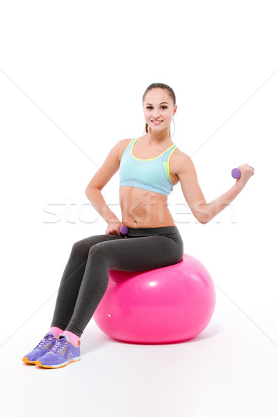 Young sportswoman exercising with dumbbells sitting on fitball Stock photo © deandrobot