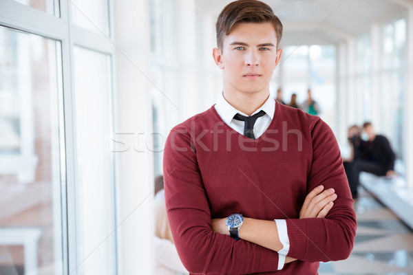 Male student standing with arms folded in university hall Stock photo © deandrobot