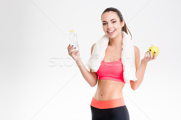 Cheerful sportswoman holding a bottle of water and an apple Stock photo © deandrobot