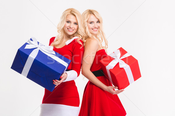 Joyful sisters twins in santa claus costumes posing with presents Stock photo © deandrobot