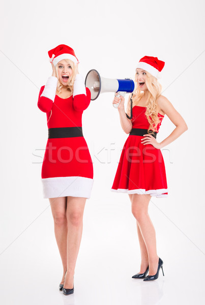 Attractive sisters twins in santa claus costumes speaking on loudspeaker  Stock photo © deandrobot