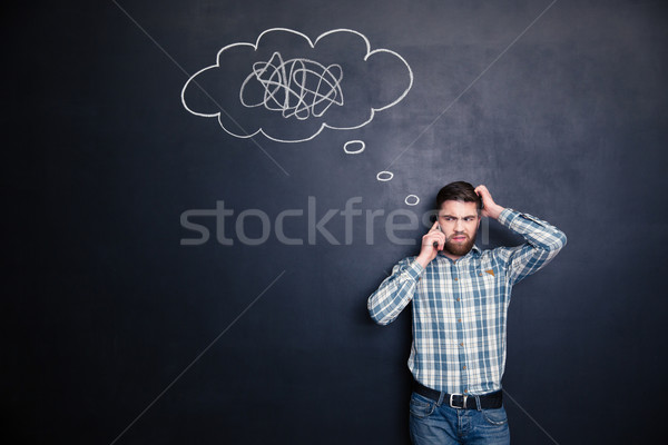 Irritated man using mobile phone standing over blackboard background Stock photo © deandrobot