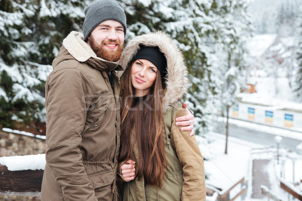 Happy beautiful couple standing together in winter Stock photo © deandrobot