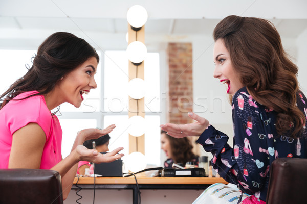 Two surprised young women sitting and talking  Stock photo © deandrobot