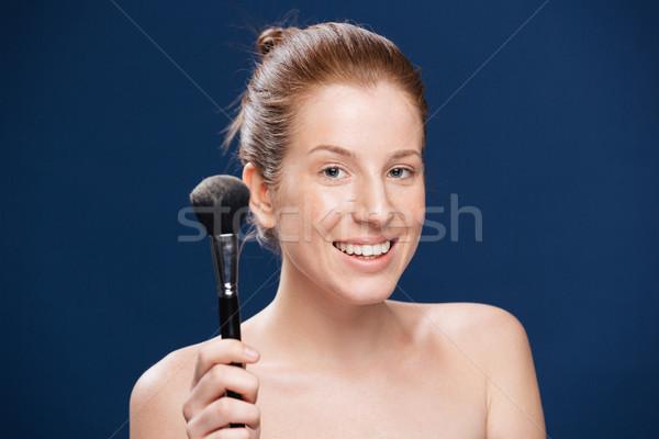 Happy woman holding makeup brush  Stock photo © deandrobot