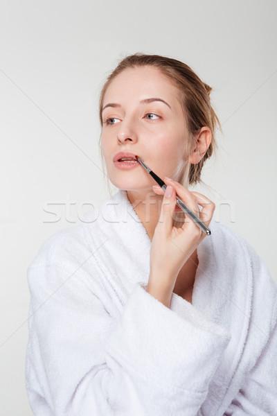 Woman applying lipstick with an applicator Stock photo © deandrobot