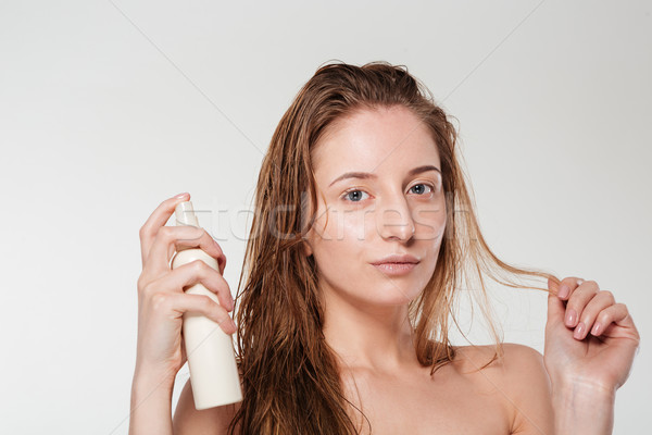 Beautiful woman spraying hairspray Stock photo © deandrobot