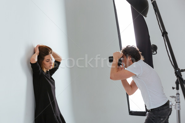 Man photographing female model in professional studio Stock photo © deandrobot