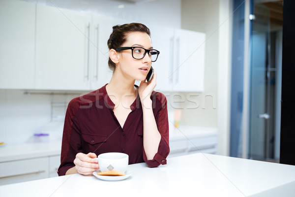 Woman in glasses drinking tea and using smartphone on kitchen Stock photo © deandrobot