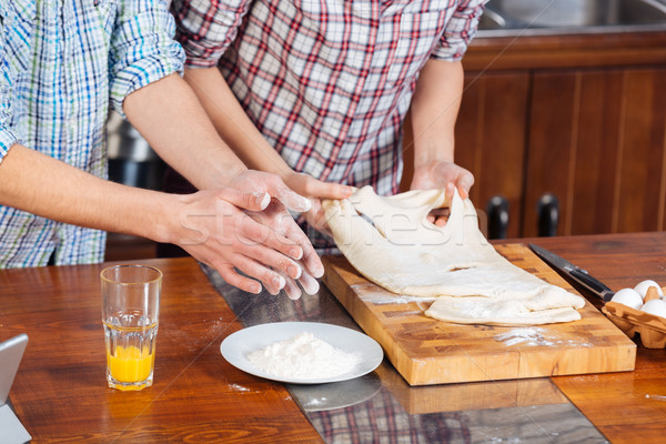 Couple standing and kneading dough on the kitchen Stock photo © deandrobot