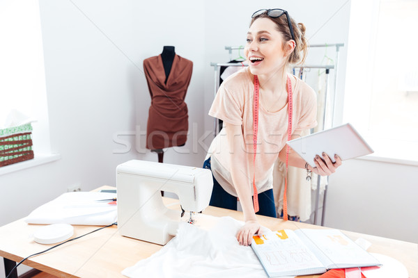 Cheerful woman seamstress with laptop at work  Stock photo © deandrobot