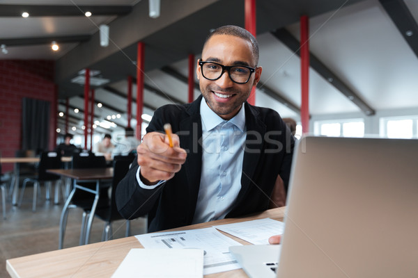 Businessman smiling and pointing at the working place Stock photo © deandrobot
