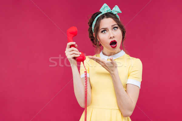Wondered beautiful pinup girl holding red receiverand talking on Stock photo © deandrobot