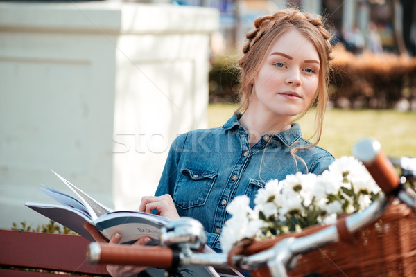 Beautiful woman with bicycle reading magazine on the bench outdoors Stock photo © deandrobot