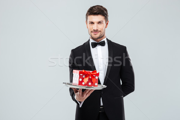 Handsome butler in tuxedo with bowtie gift box on tray Stock photo © deandrobot