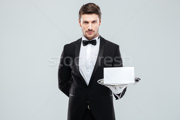 Confident young butler in tuxedo holding blank card on tray Stock photo © deandrobot