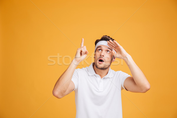Amazed attractive young sportsman looking and pointing up Stock photo © deandrobot