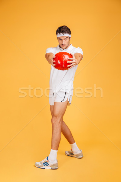 Full length of serious sports man exercising with red ball Stock photo © deandrobot