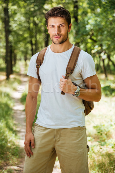 Man holding backpack and standing in forest Stock photo © deandrobot
