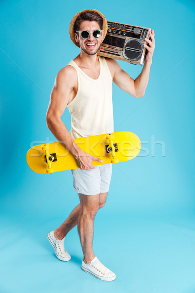 Smiling man with yellow skateboard walking and holding old boombox Stock photo © deandrobot