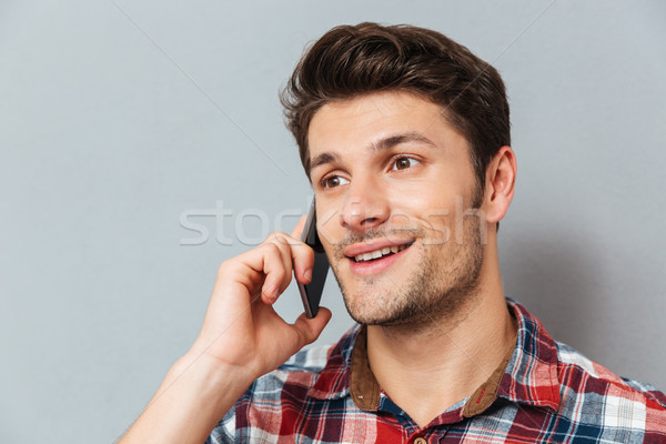 Closeup of happy young man talking on cell phone Stock photo © deandrobot