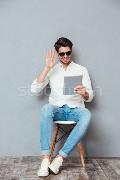 Smiling man in sunglasses using tablet and having videoconference Stock photo © deandrobot
