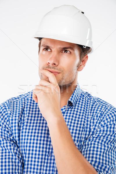 Pensativo joven edificio ingeniero casco pie Foto stock © deandrobot