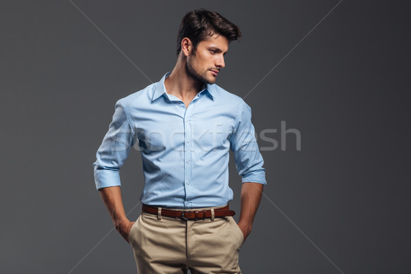 Handsome casual man standing with arms in pockets Stock photo © deandrobot