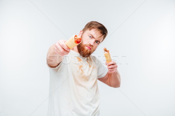 Hungry bearded man in filthy shirt holding two hotdogs Stock photo © deandrobot
