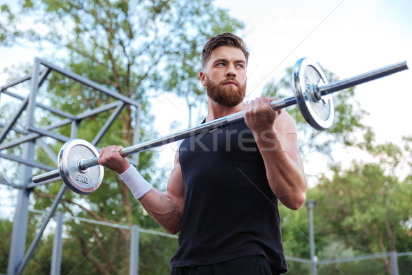 Muscular handsome man workout with barbell Stock photo © deandrobot
