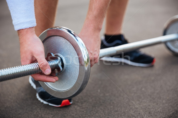 Muscular fitness man going to lift heavy barbell Stock photo © deandrobot