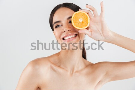 Portrait of a nude woman covering one eye with orange Stock photo © deandrobot