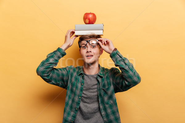 Smiling amazed man with book and apple on his head Stock photo © deandrobot
