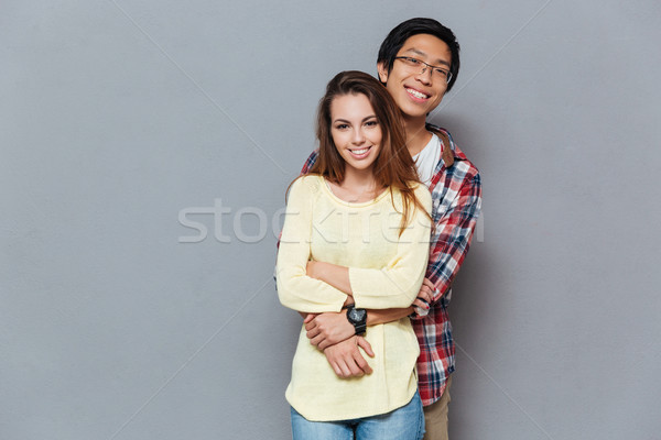 Smiling young interracial couple hugging and looking at camera Stock photo © deandrobot