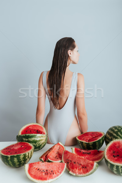 Back view of woman sitting on table with cutted watermelons Stock photo © deandrobot