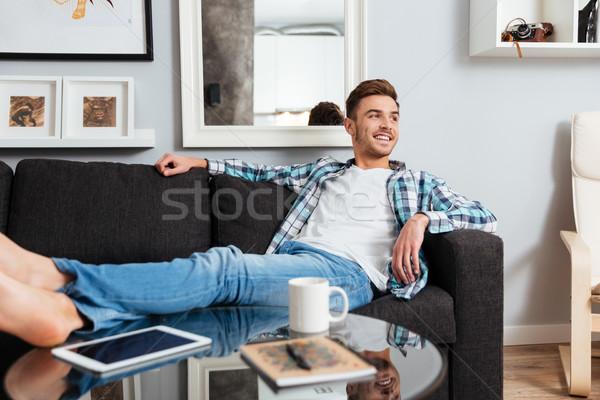 Boldog sörte férfi hazugságok kanapé néz Stock fotó © deandrobot