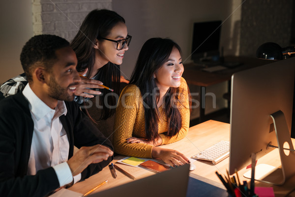 Cheerful business people working late at night in their office Stock photo © deandrobot