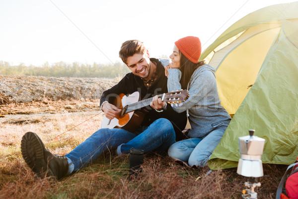 Adam oynama gitar kız arkadaş oturma çadır Stok fotoğraf © deandrobot
