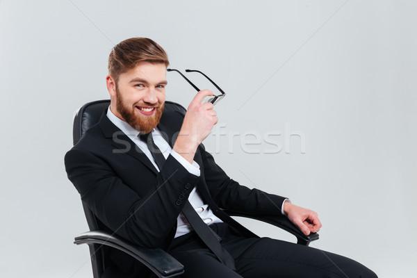 Sonriendo hombre de negocios gafas sillón barbado traje negro Foto stock © deandrobot