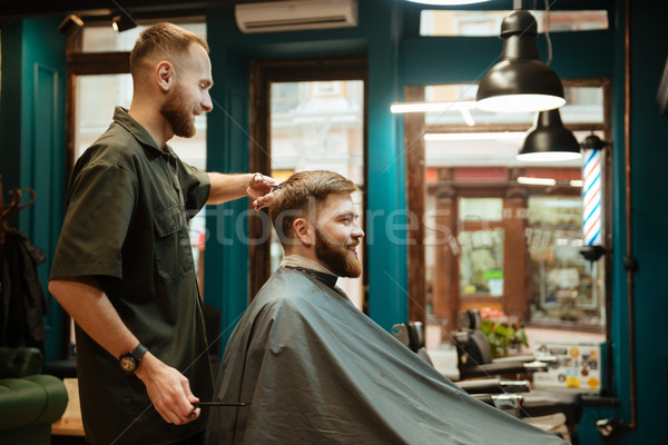 Cheerful man getting haircut by hairdresser with scissors Stock photo © deandrobot