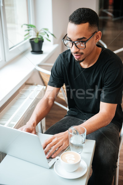 Attractive african businessman typing by laptop computer. Coworking. Stock photo © deandrobot