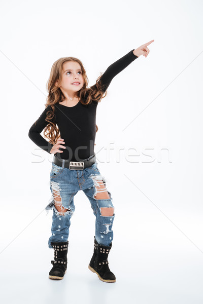 Smiling lovely little girl in torn jeans pointing away Stock photo © deandrobot