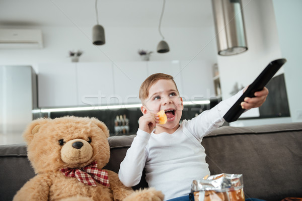 Playful boy sitting with teddy bear and watching TV Stock photo © deandrobot