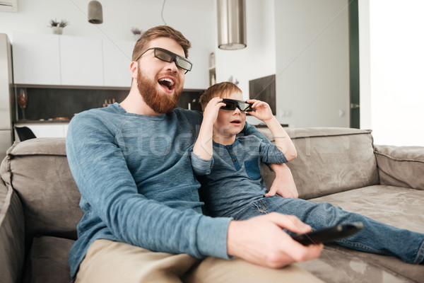 Happy bearded father watching TV with son using 3d glasses. Stock photo © deandrobot